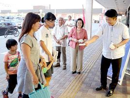 買い物客にティッシュを配り、行政相談会をPRする中山市長(右)ら=19日夕、イオンマックスバリュやいま店前