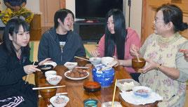 テーブルを囲んで料理を食べながら談笑する岩手の高校生=12日、宮良