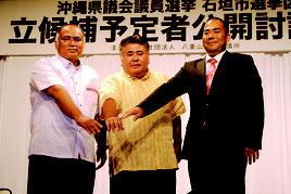 ◀立候補予定者公開討論会で握手する砂川氏、前津氏、次呂久氏(左から)=8日午後