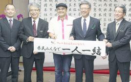 比嘉さん(中央)が「いちゃりば結」の完成を翁長知事に報告した=17日、県庁