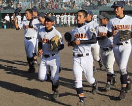 九州大会で初戦を突破し、ベンチに戻る八重高の選手ら=24日午後、鹿児島県