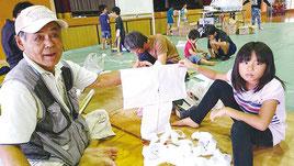 連凧作り教室の講師をつとめた富本衛さん(左)=23日、竹富小中学校体育館