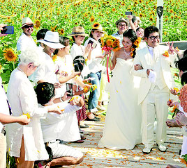 結婚式を挙げた比嘉将寿さん、桜子さんを祝福する参列者=26日午後、川平地区