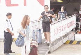石垣港に到着したスーパースターアクエリアス号から下船する台湾メディアの関係者=7日午前、同港
