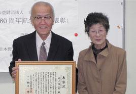 永年の野鳥保護活動が表彰され喜ぶ﨑山陽一郎さんと多津美夫人=19日午前