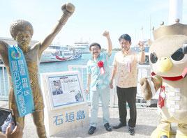記念パネルの脇で記念写真に収まる具志堅さん(左)と中山市長=離島ターミナル