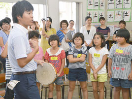 タンバリンを持ってルールを説明する平野教諭=20日、新川小学校