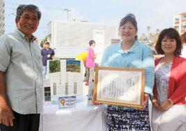 表彰状を手にする商工会女性部の浦内由美子部長と市商工会の我喜屋会長(左)=24日、奥武山公園