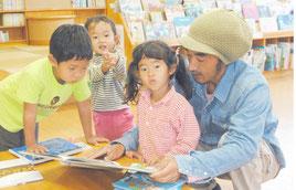 市立図書館で読書を楽しむ親子(資料写真)。北西部地区の住民は近隣校でも図書を返却できるようになる。
