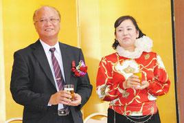 県漁連会長の就任祝賀会で、祝福に応え笑顔を見せる上原氏とりえ子夫人(26日夜)