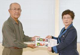 中尾さん(左)が石垣教育長に手渡した=7日、石垣市教育委員会