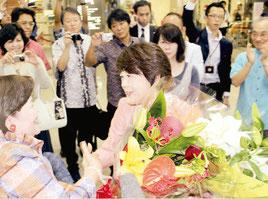 支援者らからの祝福の花束を受け取る島尻安伊子氏=10日午後、那覇空港国内線ターミナル