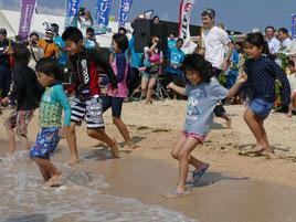 テープカット後、子どもたちが一斉に海へと駆けだした=18日午前、小浜島はいむるぶしビーチ