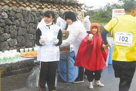 給水地点で奮闘するボランティアたち=24日午前、新川