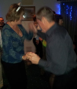 A picture of two middle aged people dancing at a birthday party.