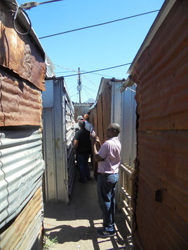 An image of the research team walking round the narrow routes of Masiphumelele informal settlement, Cape Town