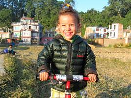Lachender Bub auf dem Laufrad. Foto: Lene Löwenherz