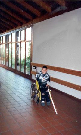 Training im Rollstuhl mit Blindenlangstock.