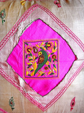 Sand-coloured, Indian, handloom, Rajastani- silk, cushion cover with embroiidered, green/yelllow parrot & leaf design on bright-pink panel, & colourful hand-stiching throughout