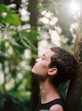 Eine Frau steht am Baum mit dem Blick nach oben