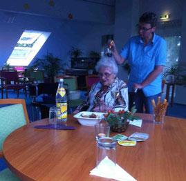 Eine Seniorin erhält eine entspannende Kopfmassage