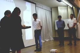 表彰を受ける、左から、三浦係長、式地主任、西村主任