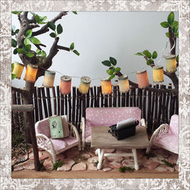 A Scenery in a typical fifties garden with vintage  miniature furniture in pink with polkadots and a garland with chinese lanterns between two trees.