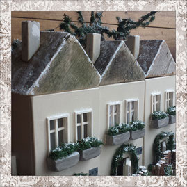 three christmas house miniatures with inner illumination in grey shabby chic colours with some pine trees behind, doors to open and a wooden fence around the ground plate