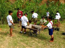 植林活動の一コマ。白いシャツに男の子は短パン、女の子はスカート、これが普通の制服。