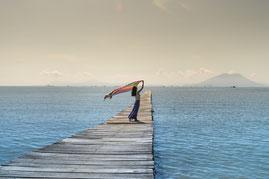 Frau auf einem Steg, der ins Meer ragt, ein buntes Tuch schwingend
