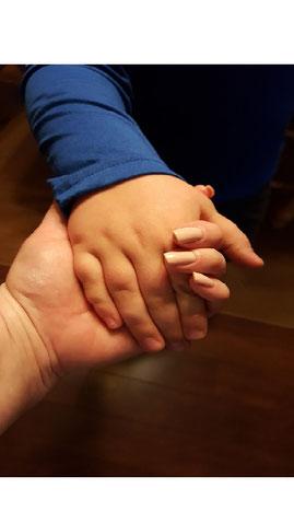 Kinderhand wird von Erwachsenenhand gehalten