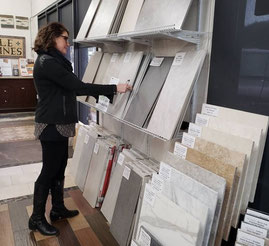 Woman in black jacket, pants, and boots looking at the in-stock tile display in Tile Lines showroom.