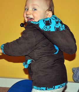 Baby trägt eine Winterjacke aus braunem Cordstoff.