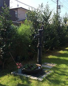 芝生のお庭にアンティックな深緑色の手押しポンプを設置しました