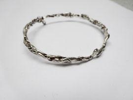 Un bracelet fin et rigide au design compressé est posé sur une feuille blanche.