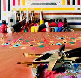 Atelier Arbeitsplatz von Andreas Alka,  alias FLoYd. Momentaufnahme einer Arbeit. Im Vordergrund einige Utensilien, wie kleine Spachtel und feine Pinsel, im Hintergrund viele unterschiedliche Farbtuben.