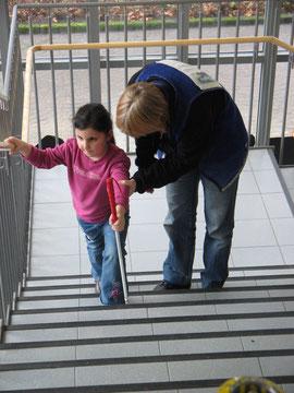 Die jüngste Teilnehmerin: 6 Jahre. Hier beim Erlernen der Treppentechnik nach oben mit Langstock in ihrer Schule. Die Trainerin unterstützt.