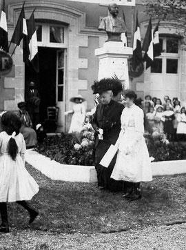 Mme Raymond venant de déposer des fleurs au pied du monument