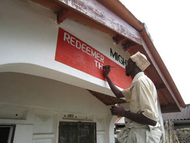 Ein Maler bringt den Namen am neuen Haus an