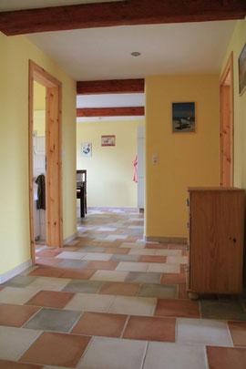 Flur mit Blick in Richtung Küche, Wohnzimmer rechts und Gäste WC links