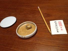 金泥を溶いた皿と筆