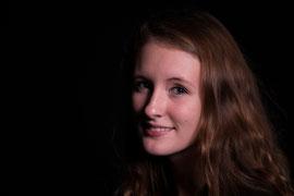 Studiofoto met zwarte achtergrond. Een jonge vrouw met lang midden bruin haar kijkt opzij in de lens.