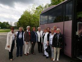 10 gutgelaunte Mitfahrerinnen am rosa Bus