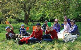Kinder der Outdoorgruppe mit Betreuern auf ihrer geheimen Wiese am Waldrand
