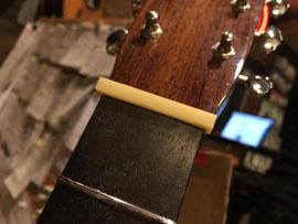 ギターにナットの材料を仮置きしている場面