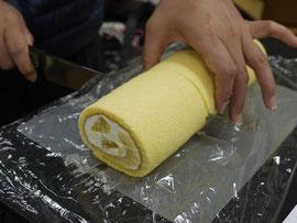 ケーキを切り分けるヤマシタさん、の手