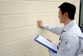 建物の調査をする塗装技術者