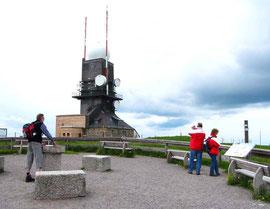 Inschrift der Tafel: Feldberg 1493 m. Sie befinden sich an der höchsten Stelle Baden-Württembergs. Hier stand um die Jahrhundertwende das Gasthaus zum Feldberg-Turm. Seit 1937 steht der Feldberg unter Naturschutz.