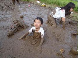 畑で泥遊びをする姿。画像は昨年の山形南部教会キャンプ