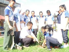 「子供の森」計画コーディネーターから苗木の植え方を教わる子どもたち